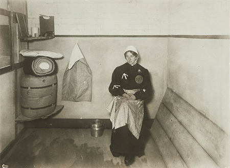 The Suffragette Elsie Howey in a replica prison cell, 1909. Replica prison uniforms were often worn by ex-suffragette prisoners at demonstrations and fund-raising bazaars to highlight the conditions under which imprisoned Suffragettes were held. This image was probably taken at the Women's Exhibition held at Princes Skating Rink in May 1909 where a 'Prison Life' exhibit included a replica prison cell 'peopled' by Suffragettes dressed in replica prison clothing and taking part in prison activities such as sewing.