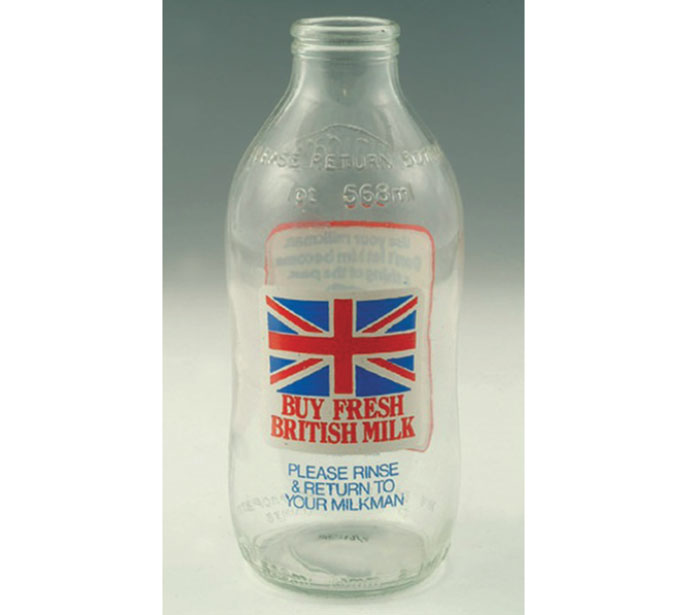 A clear glass milk bottle with a Union Flag and the title 'But Fresh British Milk' written on it.