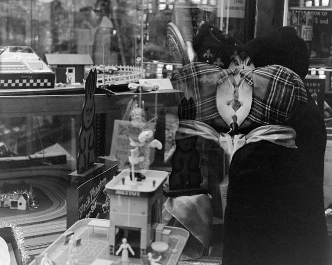 A boy looks in at the window of Hamley's toy display, Christmas 1963