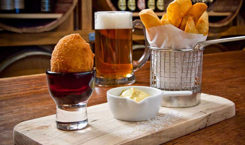 Pub food served on a wooden tray with a pint of beer.
