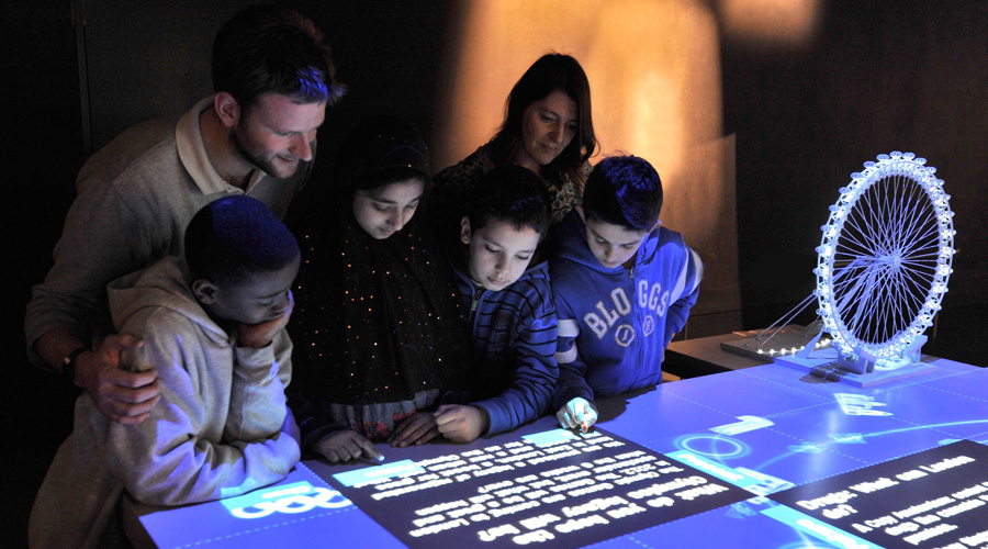 Group of adults and children looking at digital display