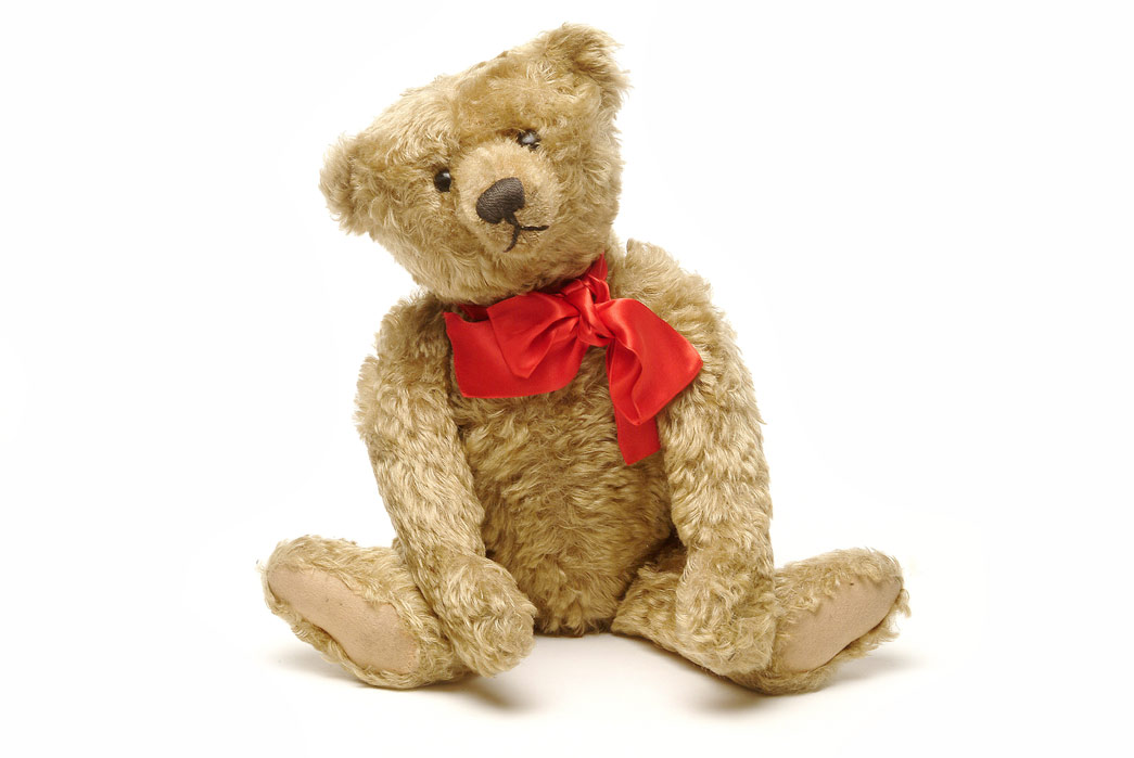 A sandy coloured,jointed teddy bear with button eyes, hump on its back and a Steiff metal button in its ear. There is a red bow around its neck. The donor's eldest son received this teddy bear as a present in 1907, when it was the latest fashionable toy. It makes a growling sound when the stomach is pressed and was made by the Steiff Company in Germany. Sandy coloured plush, probably Excelsior stuffed, with jointed arms and legs, button eyes, hump on back and Steiff metal button in ear. In 1902, Margarete Stieff, a disabled german toy manufacturer, made the first plush toy bears. The name comes from a cartoon of US president Theodore ('Teddy') Roosevelt, who refused to shoot a tethered bear. Teddy bears were an instant hit and have become a traditional childhood toy, beloved by millions.