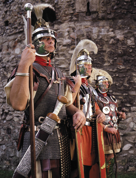 Close up of Roman soldiers, Ermin Street Guard photographed next to London Wall. Actors re-enacting a line of Roman soldiers wearing uniform, helmets and badges of office.