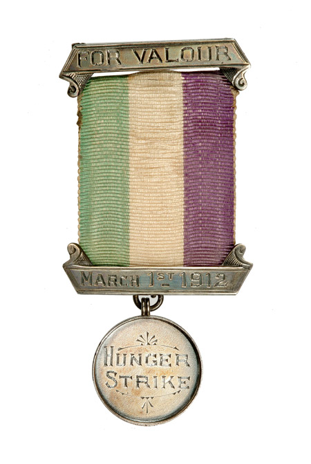 This image shows a suffragette prisoner's silver hunger strike medal with purple, white and green ribbon. It was presented to Emmeline Pankhurst to commemorate her hunger strike when serving a 9 month sentence in Holloway jail for 'conspiracy to incite persons to commit damage to property'.