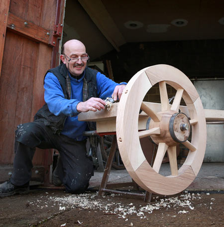 View of Croford's coachbuilders making wooden wheel of the fire engine.