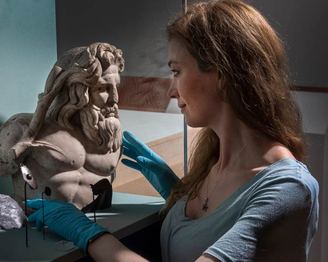 Curator installs a Roman god bust into a glass display case.