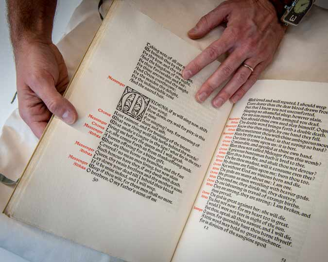 Close up of two hands holding a rare medieval manuscript.
