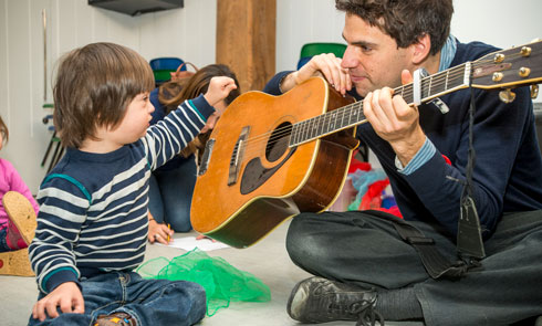 A child touches a guitar at a session for under-5s.