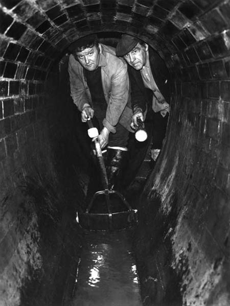 Sewer cleaners, Sam Luck (left) and Robert Attwood, beneath Lower Thames Street in a 19th century brick sewer, 1974. The men had worked in the sewers for 18 and 23 years respectively and both had previously been dustmen.