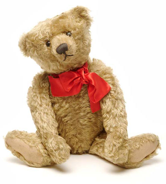 The donor's eldest son received this teddy bear as a present in 1907, when it was the latest fashionable toy. Sandy coloured plush, probably Excelsior stuffed, with jointed arms and legs, button eyes, hump on back and Steiff metal button in ear.