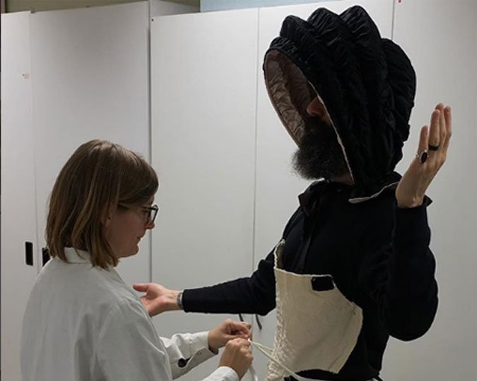 Curator Tim Long is measured for an 18th century bonnet