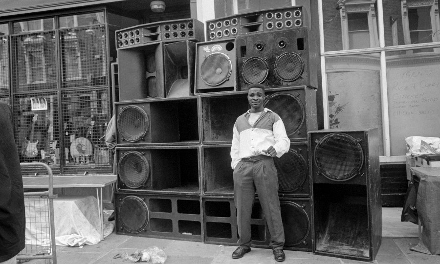 Black and white image of a man standing in front of soundsystem