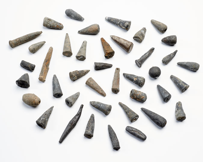 A collection of 15th-century lead fishing weights found on the Thames foreshore at Brook's Wharf, City of London. Many of them were mass-produced in moulds and may have been from sea-fishing nets.