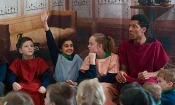 Performers in a Roman workshop for primary pupils in a school hall.