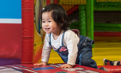An under-5-year-old smiling in a soft play area.