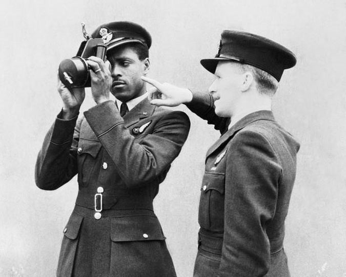 A black RAF officer holds a navigational instrument, being instructed in its use by another white officer. IWM.