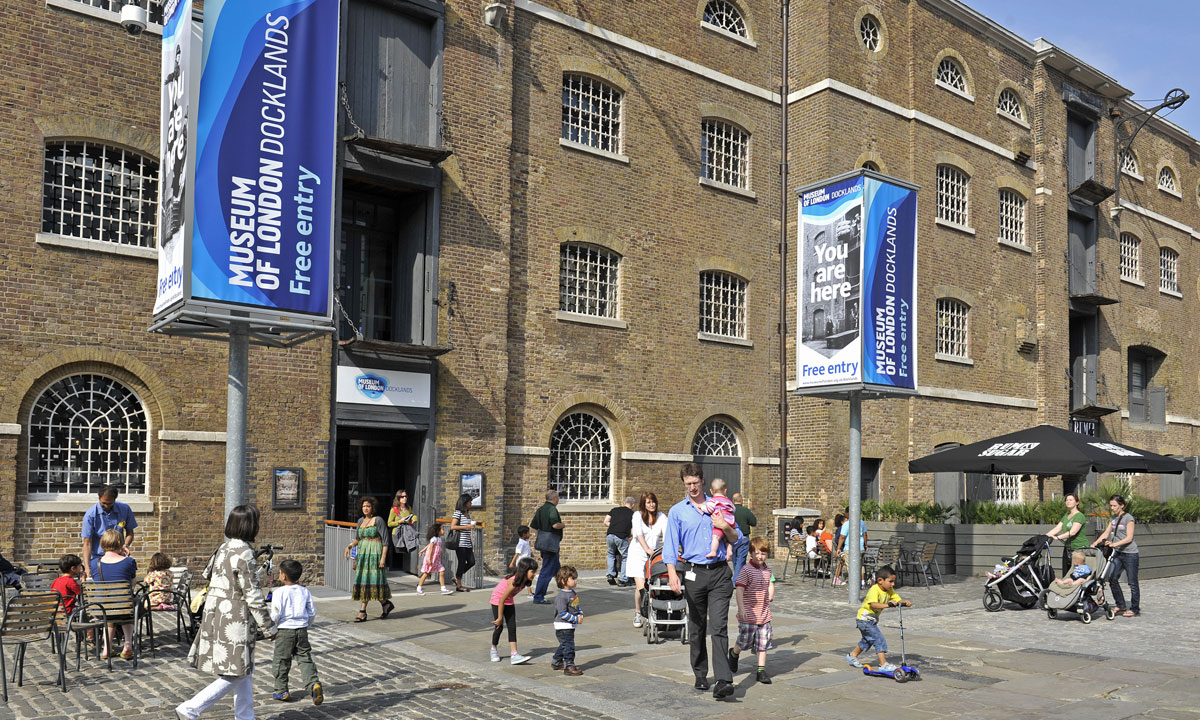 An outside view of the Museum of London Docklands with families in view.