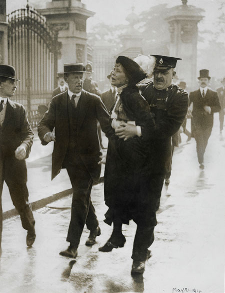 Emmeline Pankhurst being arrested while trying to present a petition to the King at Buckingham Palace, 21 May 1914. As she was being carried past a group of reporters Emmeline called out 'Arrested at the gates of the Palace. Tell the King'.