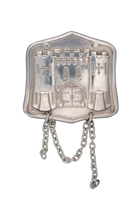 A silver badge presented to Muriel Matters by the Women's Freedom League on her release from Holloway prison in 1908. Engraved M.M. October 28 and November 28 1908. The brooch depicts in stylised relief the entrance to Holloway prison.