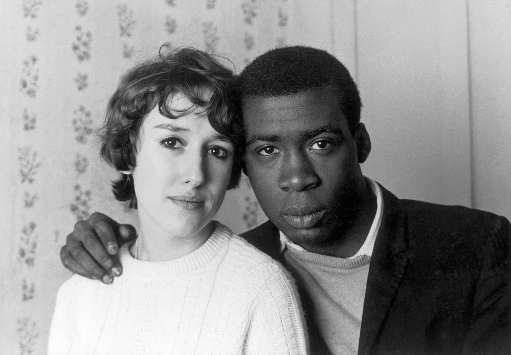 This photograph, entitled 'Notting Hill Couple', is a close-up of a black man and a white woman. He rests his hand on her shoulder while she tilts her head towards his. Both look directly at the camera.