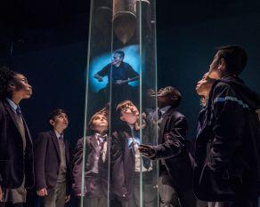 Group of schoolchildren view an interactive exhibit on the Second World War.