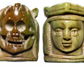 Two sides of a medieval rosary bead, designed with a face on one side and a skull on the other.