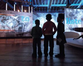 Three children watch a sound and light show in the Sugar and Slavery gallery at the Museum of London Docklands.