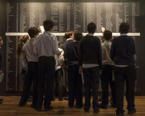 Young visitors to the Museum of London Docklands view the names of slave ships that sailed from London.